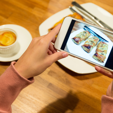 Arms of a person holding a mobile phone taking a photo of a plate of food. There is a coffee to the left of the person's left arm.